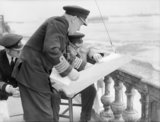 Captain H Hickling, commanding naval forces at Arromanches, shows a plan of the Mulberry artificial harbour to Winston Churchill, July 1944.