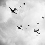 Paratroops drop from Dakota aircraft over the outskirts of Arnhem during Operation 'Market Garden', 17 September 1944.