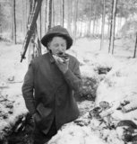 A British soldier eats his midday meal in a trench in the snow, while manning part of the front line along the River Maas in Holland, 8 January 1945.