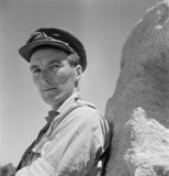 Cecil Beaton portrait of a Royal Artillery officer leaning against a rock in the Western Desert, 1942.