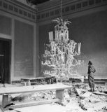 Sergeant R S Baker of the Army Film & Photographic Unit (AFPU) looks at one of the giant chandeliers in the ruins of Hitler's Reich Chancellery in Berlin, 3 July 1945.