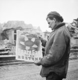 A soldier standing in the ruins of Kleve in Germany, reading a German poster calling for civilians to conserve fuel supplies for the war effort, 13 February 1945.