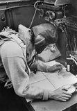 A Cecil Beaton photograph of the navigator working at his chart table in an RAF Stirling bomber, 1941.