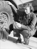 A member of the Auxiliary Territorial Service (ATS) tests the air pressure of the tyre on a large lorry as part of her driver training course in 1942.
