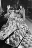 A woman buys cakes from a patisserie counter of a large London department store in 1942.
