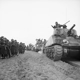Sherman tanks of 23rd Armoured Brigade come ashore with infantry at Anzio, Italy, 22 January 1944.