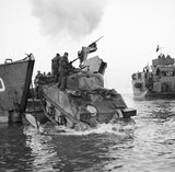 A Sherman tank of 23rd Armoured Brigade coming ashore from a landing craft at Anzio, Italy, 22 January 1944.