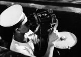 A look-out on board a Royal Indian Navy sloop scans the horizon using binoculars during anti-submarine escort duties in the Indian Ocean, 1945.