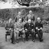 Winston Churchill with his Chiefs of Staff at 10 Downing Street, 7 May 1945. Seated are Sir Charles Portal; Sir Alan Brooke; Sir Andrew Cunningham. Standing are Major General L C Hollis and General Sir Hastings Ismay.