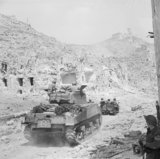 A British Sherman tank and jeep of 4th Armoured Brigade entering the ruins of Cassino, Italy, 18 May 1944.