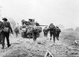Sherman DD tanks of 'B' Squadron, 13th/18th Royal Hussars support men of No. 4 Army Commando advancing towards Ouistreham on D-Day, 6 June 1944.