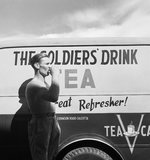 Cecil Beaton photograph of a British soldier drinking tea next to a Red Cross mobile tea wagon at Calcutta airport in 1944.