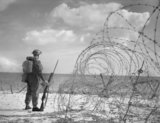A symbolic photograph of British soldier standing guard on a beach in southern England, 7 October 1940.