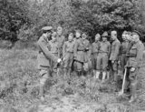 Men of the American 77th Division receiving instruction in camouflage and sniping from the British at Moulle, 22 May 1918. A camouflaged sniper is lying concealed between the officer and the men.
