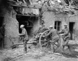 Gunners of the Royal Field Artillery manhandle an 18-pounder field gun into a firing position beside a ruined house in the village of Saint Floris, 2 May 1918.