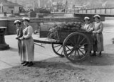 Four ratings of the Women's Royal Navala Service (WRNS) with a cart full of finished floats for anti-mine nets on the quayside at Lowestoft in 1918.