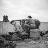 Paras from 5th (Scots) Parachute Battalion, 2nd Parachute Brigade, fire a Vickers machine gun from a rooftop in Athens during operations against members of ELAS, 7 December 1944.