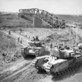 Churchill tanks of 21st Army Tank Brigade cross the River Reno close to a destroyed railway bridge near Bastia, Italy, 18 April 1945.