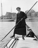 Gladys Wilburn of the Womens Royal Naval Service (WRNS) using a boat-hook to push her motor boat, the BALMACAAN, away from the shore at Southwick harbour, 1918.