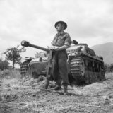 Fusilier Jefferson of 'C' Company, 2nd Lancashire Fusiliers, in front of a German StuG III assault gun which he knocked out with a PIAT, May 1944.