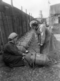 Two ratings of the Women's Royal Naval Service (WRNS) checking the air pressure in Electric Contact mines on the quayside at Lowestoft in 1918.
