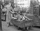 Two women munitions workers with a truck load of shell cases in the New Case Shop at the Royal Arsenal, Woolwich during the First World War.