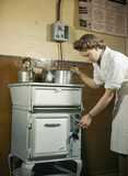 Private Catherine Thomas of the Auxiliary Terrotorial Service using an oven during a domestic science course for service women at Avondale Park School, Notting Hill Gate, London, 1945.