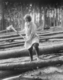 A member of the Women's Forestry Corps uses an axe to mark felled tree trunks for sawing during the First World War.