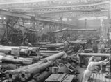 A busy howitzer shop at Coventry Ordnance Works. Men and women work together as several gun barrels are transported overhead by pulleys.