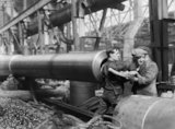 A female munitions worker is lifted into the barrel of a 15-inch naval gun manufactured at the Ordnance Works, Coventry, during the First World War, in order to clean the rifling.