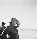 Prime Minister, Mr Winston Churchill wearing sun helmet, viewing the Alamein position.