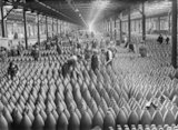 Workers, both male and female, amid rows and rows of shells in a large warehouse at the National Filling Factory, Chilwell.
