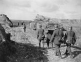 German prisoners, carring a wounded man, follow a British tank near Moeuvres, 27 September 1918.
