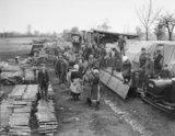 Italian girl workers detraining from light railway trucks at a railhead ammunition dump.