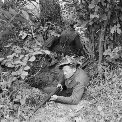 Men of the 5/7th Gordon Highlanders occupy a defensive position in a hedgerow, Normandy, 17 June 1944.
