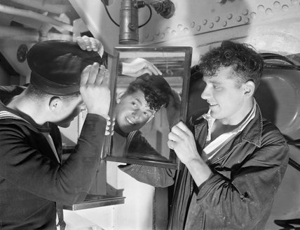 Two sailors on HMS ANSON smartening up ready for the liberty boat to take them ashore at Scapa Flow, October 1942.