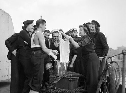 Marion Richards, a rating of the Women's Royal Naval Service in Plymouth shows a sailor from a moored destroyer how to wash clothes using a bucket, November 1944.