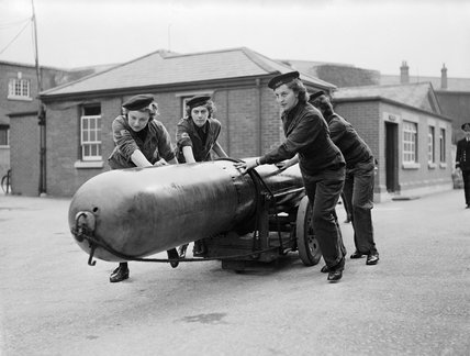 Members of the Women's Royal Naval Service (WRNS) move a torpedo for loading into a submarine at Portsmouth, 29 September 1943.