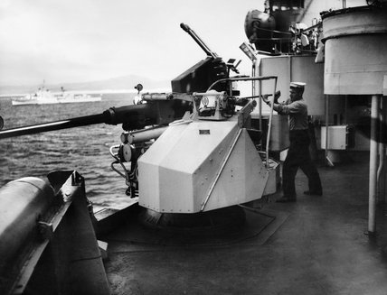 A Bofors gun being cleaned on board HMS SHEFFIELD on a NATO exercise in the Mediterranean, April 1958