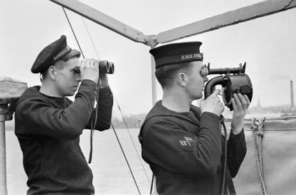 A British sailor signalling by hand held flash lamp aboard the Dutch Torpedo Boat Z 5 as it serves with the British Fleet. His dutch shipmate is looking out for the reply through a pair of binoculars, 1941.