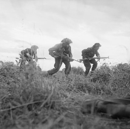 Infantry of 8 Rifle Brigade (Motor), 11th Armoured Divsion, move forward cautiously near Eterville, Normandy, 29 June 1944.