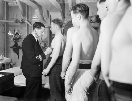 A Royal Navy surgeon lieutenant examining sailors who have come aboard HMS RODNEY, October 1940.