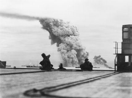 Billowing smoke marks the end of the ammunition ship MARY LUCKENBACH, seen from the deck of the carrier HMS AVENGER, during convoy PQ 18 to Russia, 13 September 1942.