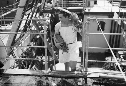 A French sailor carrying fresh pineapples on board the submarine depot ship HMS MERCATOR at Freetown, Sierra Leone, August 1943.