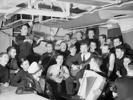Sailors enjoy a Christmas sing-song on the mess deck of a warship of the Home Fleet at Scapa Flow, 12 December 1942.