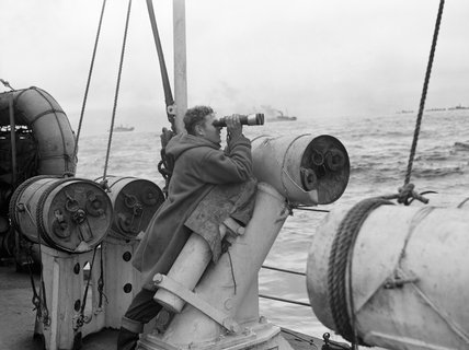 Leaning against a depth charge thrower, the quarterdeck lookout on board HMS VISCOUNT searches the sea for submarines, 1942.