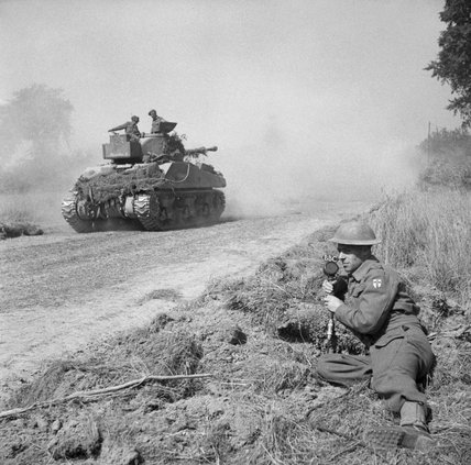 Pierre Lefevre, a Free French war correspondent, making a broadcast as a Sherman Firefly tank moves up to the battle area, Normandy, 5 August 1944.