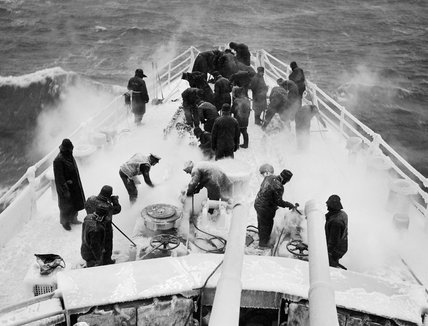 Sailors using steam hoses to clear ice from anchor chains and winches on board HMS SCYLLA during a cold spell on patrol in the Atlantic, February 1943.
