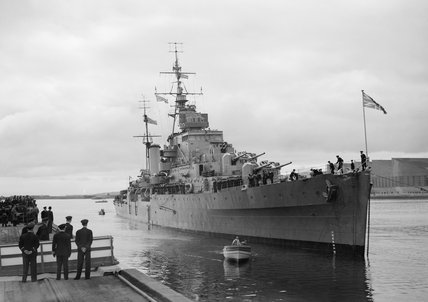The cruiser HMS PHOEBE with HM King George VI and HM Queen Elizabeth on board, coming alongside the quay at Belfast, 1942.