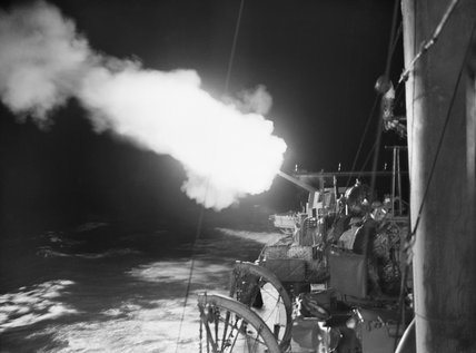 A 4.7-inch gun onboard HMS JUPITER firing on enemy shipping in the port of Cherbourg, on the night of 10/11 October 1940.